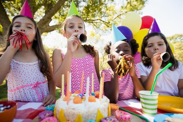 Crianças expirando em um trompete de aniversário durante uma festa de aniversário Foto Premium