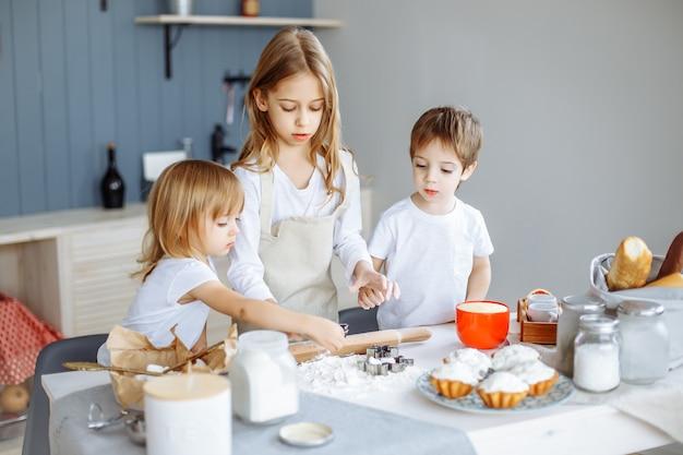 Crianças fazendo biscoitos na cozinha. Foto Premium