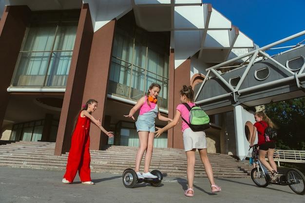 Crianças felizes brincando nas ruas da cidade em um dia ensolarado de verão em frente a um edifício moderno. grupo de crianças ou adolescentes felizes se divertindo juntos Foto gratuita