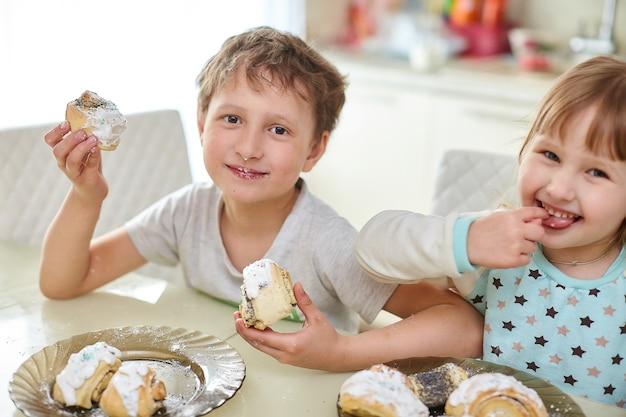 Crianças felizes comem bolos na cozinha brilhante à mesa Foto Premium