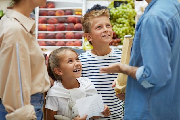 Crianças felizes, compras com os pais no supermercado Foto Premium