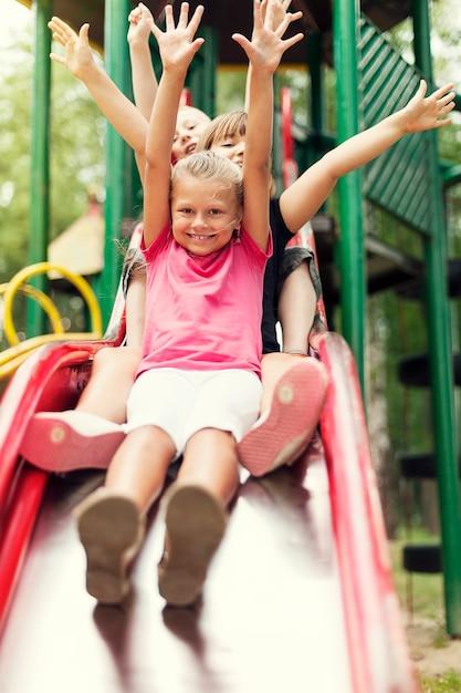 Crianças felizes deslizam no parquinho Foto gratuita
