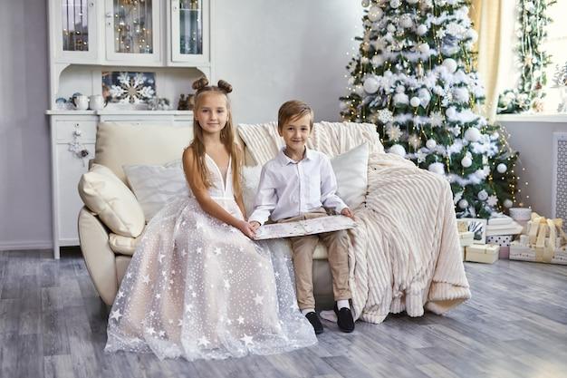 Crianças felizes e bem vestidas sentadas no sofá Foto Premium