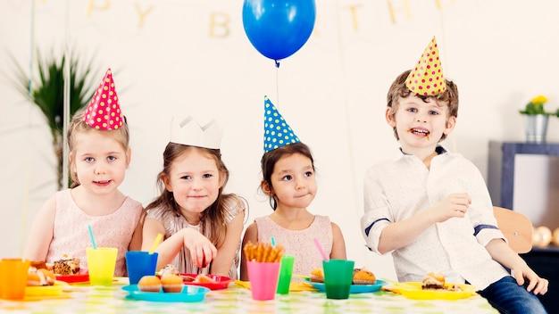Crianças felizes em tampas coloridas Foto gratuita