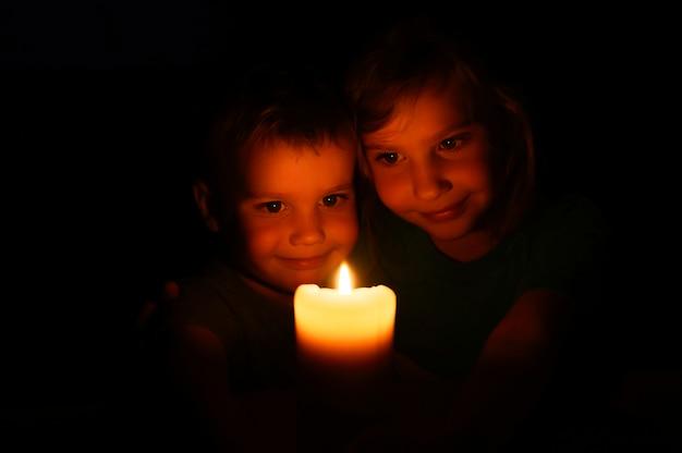 Crianças felizes irmãos menino e menina admira uma vela acesa de cera à noite em casa Foto Premium