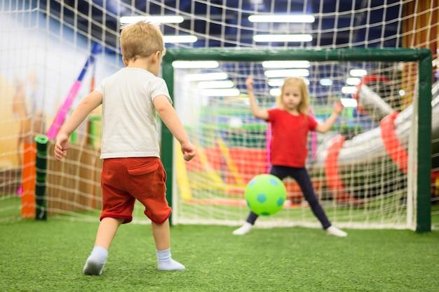 Crianças felizes jogando futebol dentro de casa Foto gratuita