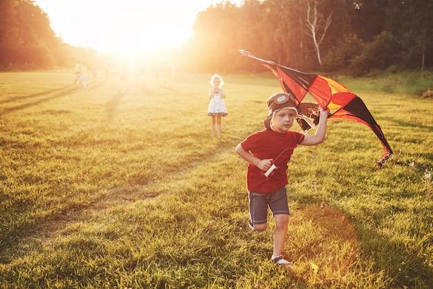 Crianças felizes lançar uma pipa no campo ao pôr do sol. menino e menina nas férias de verão Foto gratuita