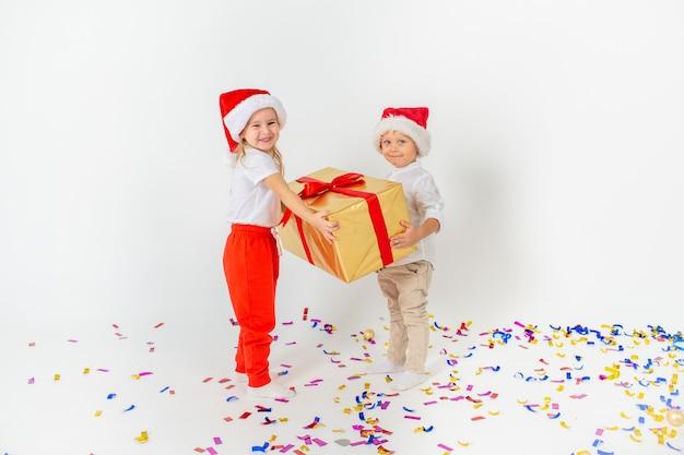 Crianças felizes no chapéu de papai noel segurando a caixa de presente grande. isolado no fundo branco venda, férias, natal, ano novo, conceito de natal. Foto Premium