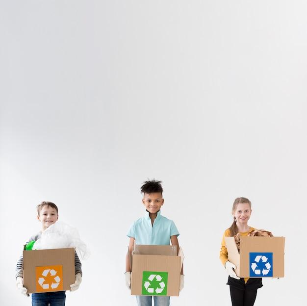 Crianças felizes, segurando caixas de reciclagem Foto gratuita