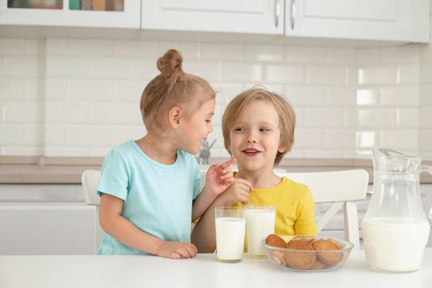 Crianças fofas bebendo leite em casa Foto Premium