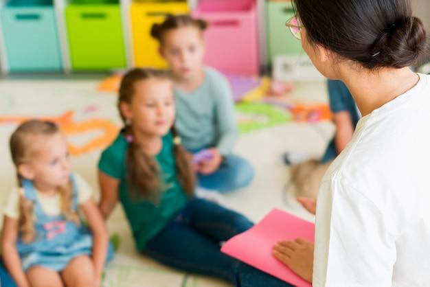 Crianças fora de foco prestando atenção ao professor Foto gratuita