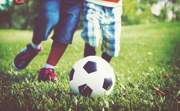 Crianças jogando futebol em uma grama Foto gratuita