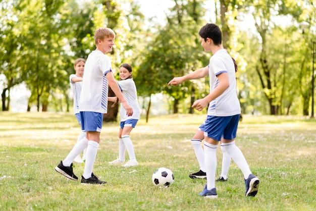 Crianças jogando futebol juntas Foto gratuita