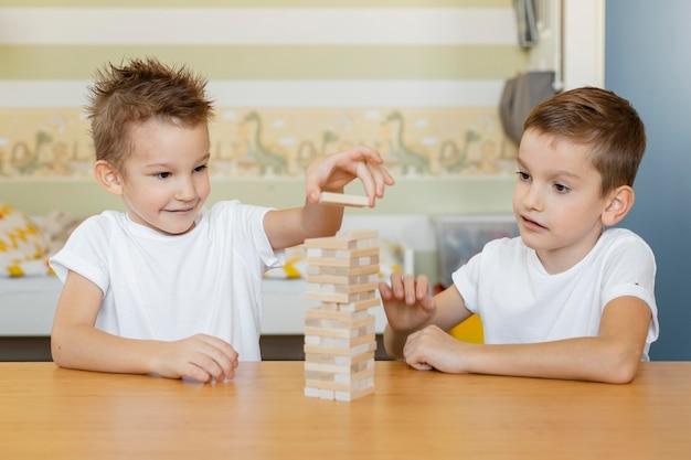 Crianças jogando um jogo de torre de madeira Foto gratuita