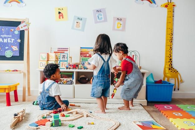 Crianças jovens que apreciam na sala de jogos Foto Premium