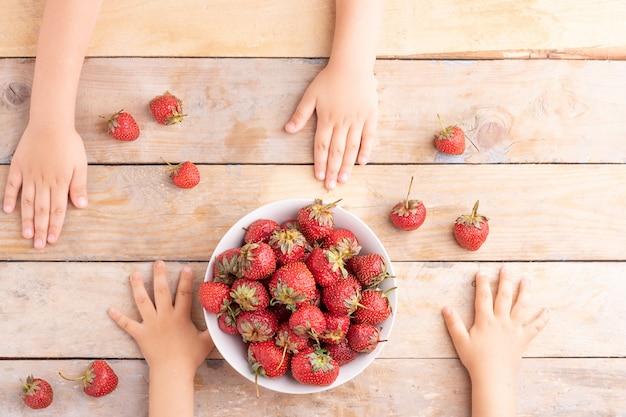 Crianças mãos perto de tigela branca com morangos, vista superior Foto Premium