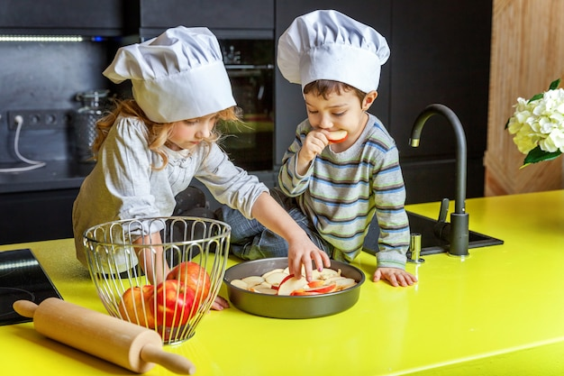 Crianças, menina, e, menino, com, chapéu cozinheiro, preparar, assar, maçã caseiro, torta, em, cozinha Foto Premium