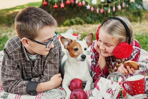 Crianças menino e menina com um cachorro jack russell terrier perto de uma árvore de natal com presentes, Foto Premium