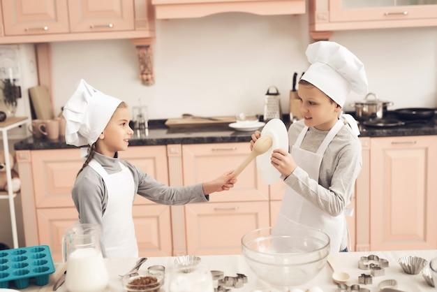 Crianças menino e menina espera cortadores de biscoito na cozinha. Foto Premium