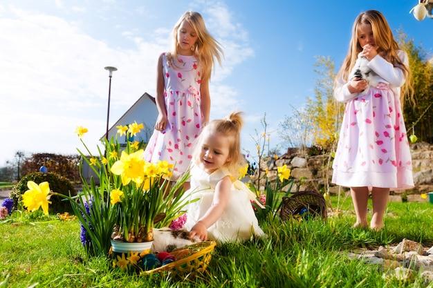 Crianças na caça aos ovos de páscoa com coelho Foto Premium