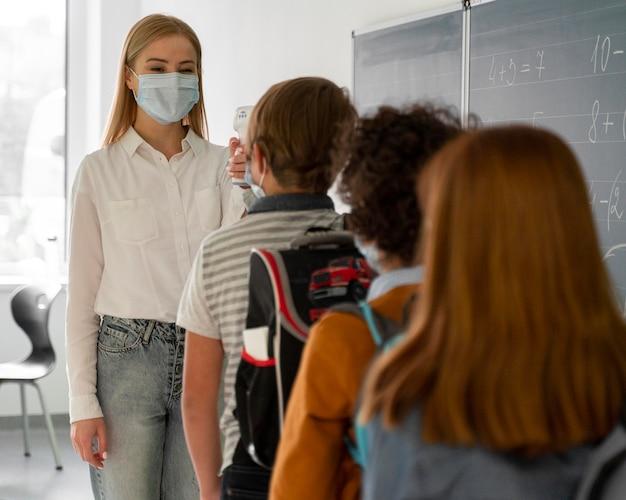 Crianças na escola alinhadas para verificação de temperatura por professora Foto Premium