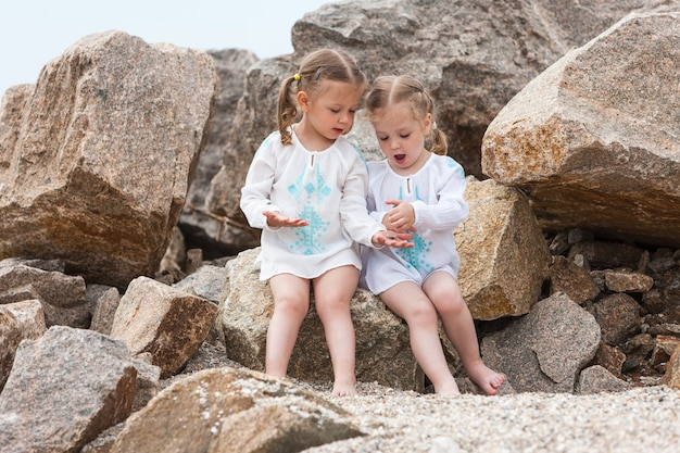 Crianças na praia do mar. gêmeos sentados contra pedras e água do mar. Foto gratuita
