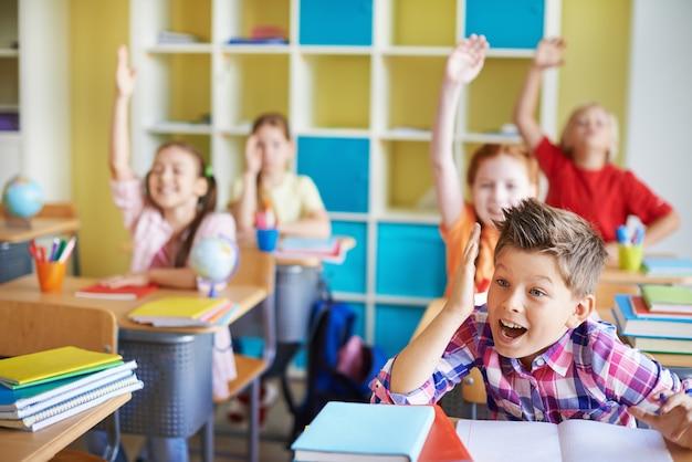 Crianças na sala de aula com as mãos para cima deles Foto gratuita