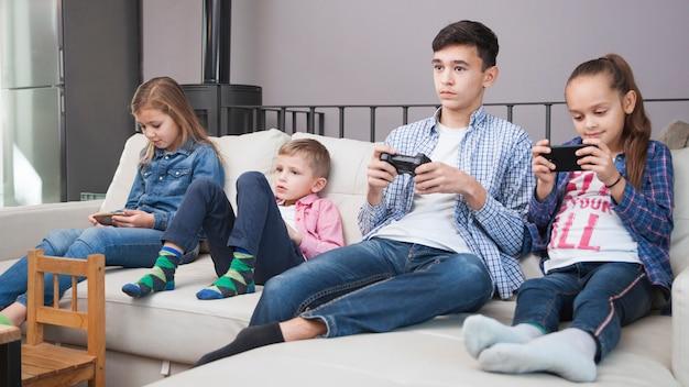 Crianças navegando smartphones perto de adolescente com controlador Foto gratuita