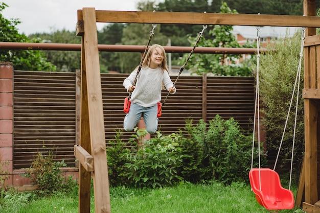 Crianças no balanço. garota balançando em um balanço no quintal. diversão de verão. Foto gratuita