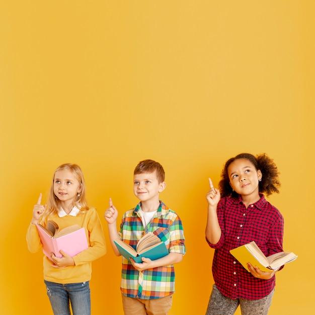 Crianças no espaço da cópia apontando acima Foto gratuita