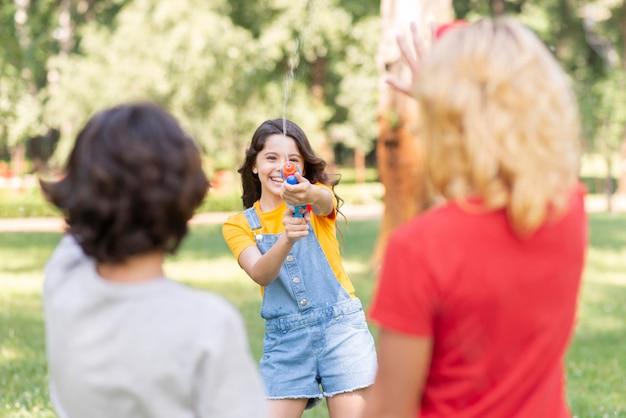 Crianças no parque brincando com pistola de água Foto gratuita