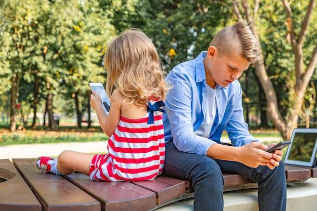 Crianças ocupadas olhando para seus telefones, mandando sms e brincando sentadas do lado de fora Foto Premium