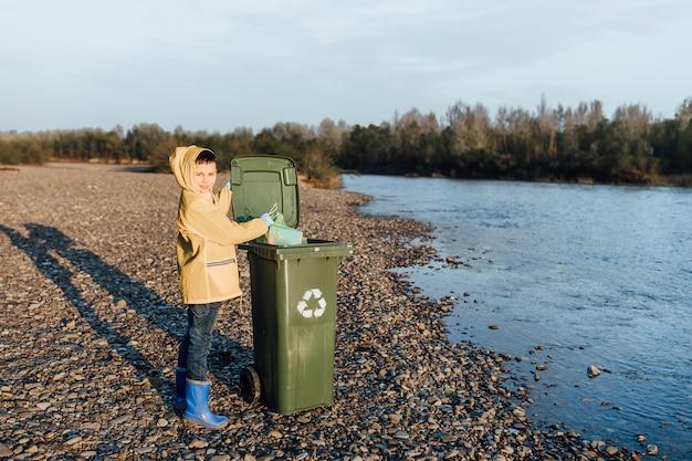 Crianças pegando o plástico vazio da garrafa no saco de lixo, ajuda voluntária. Foto Premium