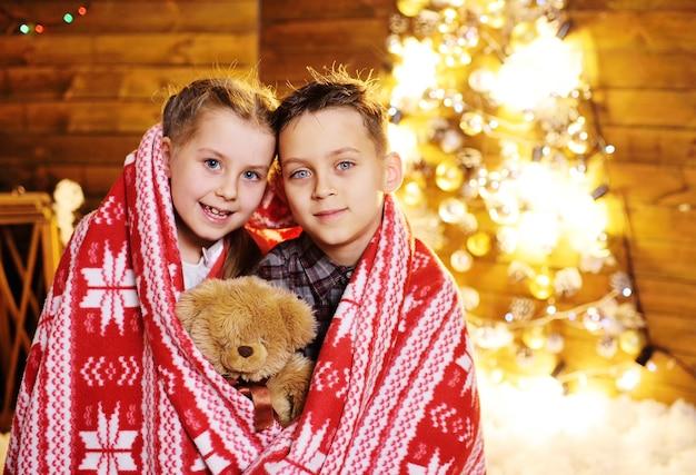 Crianças pequenas - um menino e uma menina cobertos com um cobertor vermelho quente no estilo escandinavo com um urso de brinquedo nas mãos Foto Premium