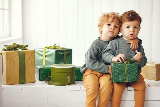 Crianças perto de árvore de natal em um suéter cinza Foto gratuita