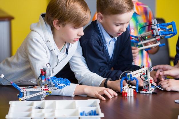 Crianças positivas brincam e montam o construtor no quarto das crianças. Foto Premium