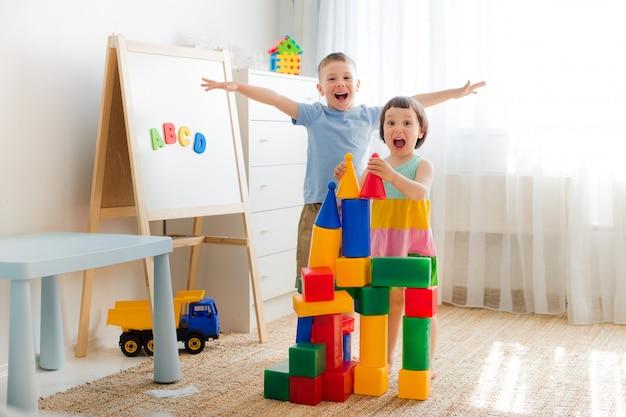 Crianças prées-escolar felizes brincam com blocos de brinquedo. Foto Premium