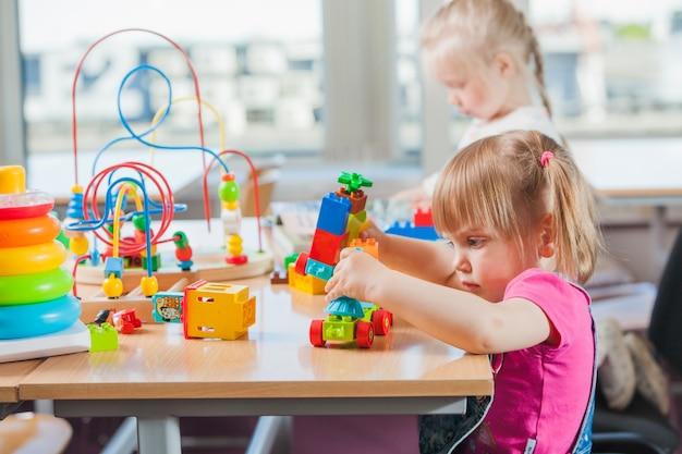 Crianças que brincam no jardim de infância Foto Premium