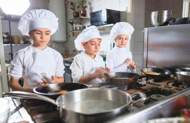 Crianças que cozinham o almoço em uma cozinha do restaurante. Foto Premium