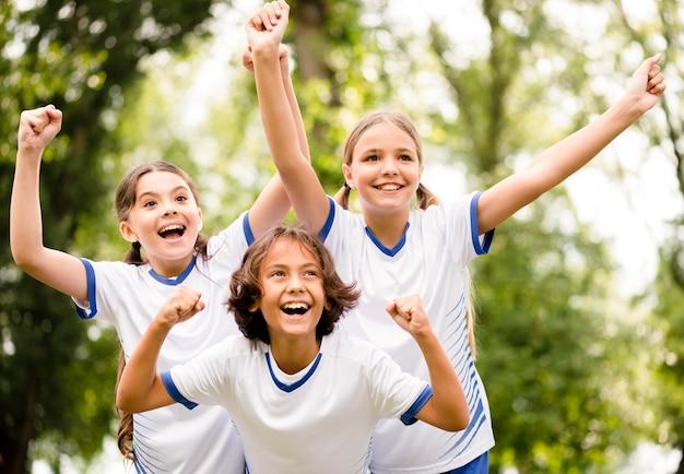 Crianças recebendo um troféu após vencer uma partida de futebol lá fora Foto gratuita