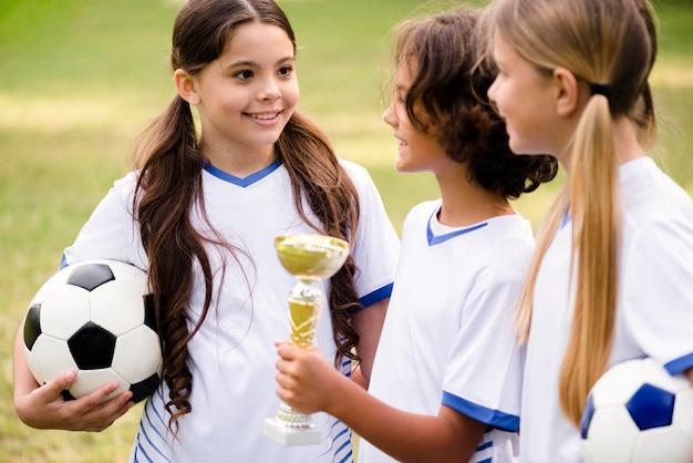 Crianças recebendo um troféu após vencer uma partida de futebol Foto gratuita