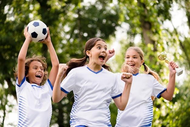 Crianças recebendo um troféu depois de vencer uma partida de futebol ao ar livre Foto gratuita