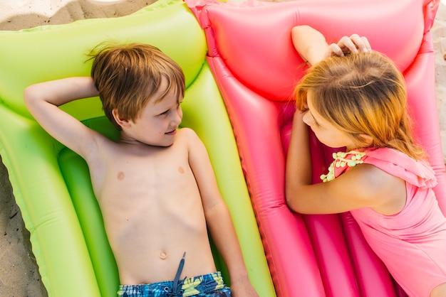 Crianças relaxando em colchões de ar na praia Foto gratuita