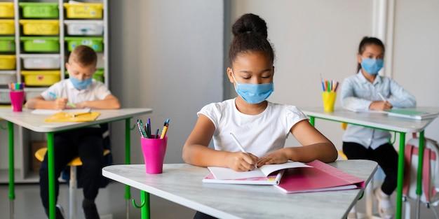 Crianças se protegendo com máscaras médicas Foto gratuita