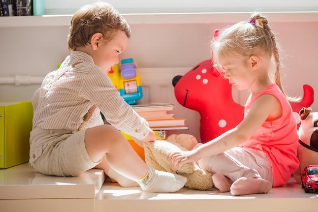 Crianças sentadas brincando com brinquedo fofo Foto gratuita