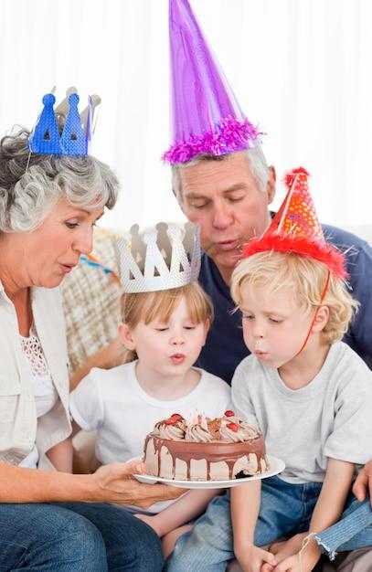Crianças soprando no bolo de aniversário Foto Premium