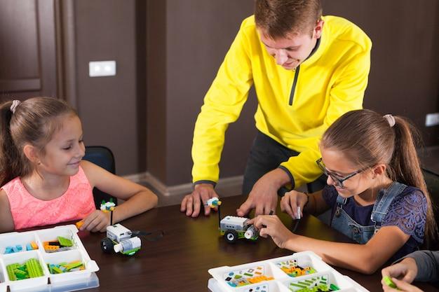 Crianças sorridentes alegres estão construindo um construtor. Foto Premium
