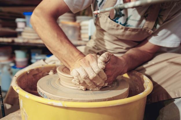 Criando um pote ou vaso de barro branco close-up Foto gratuita