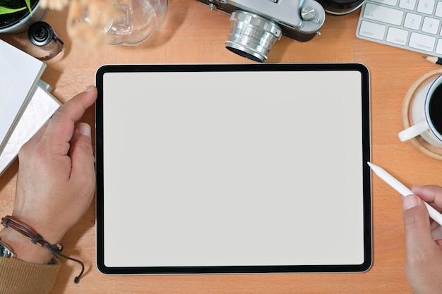 Criativa elegante mão segurando o tablet de desenho de tela em branco e lápis Foto Premium