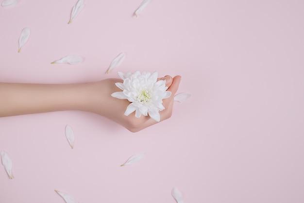 Criativo e moda arte pele cuidados de mãos e flores brancas na mão das mulheres. Foto Premium
